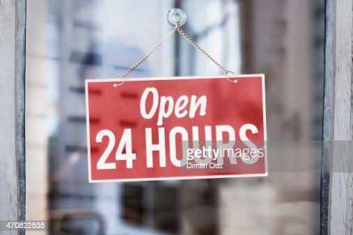 Open 24 hours sign on glass of shop door
