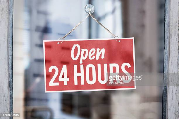 Open 24 hours sign on glass of shop door