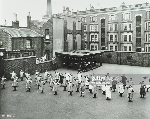 Open air exercise class Ben Jonson School Stepney London 1911 A class of girls perform physical drill in the playground A classroom is set up under a...
