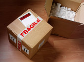 Open and closed cardboard boxes wrapped with fragile labels and polystyrene, to show you care.