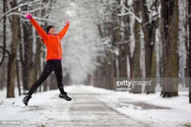 Offenen Sie armen - glückliche Frau springen mit offenen Armen im winter