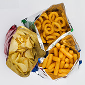 top view of three open bags of chips of different sizes, colors and textures