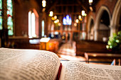 Bible open at the book of John inside an Anglican Church of England church. The focus is on the foreground of the bible, while in the background, defocused, are the pews and arches of the historic eig