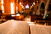 Bible open at the book of John on an altar inside an Anglican Church of England church. The focus is on the foreground of the bible, while in the background, defocused, are the wooden pews and stone a