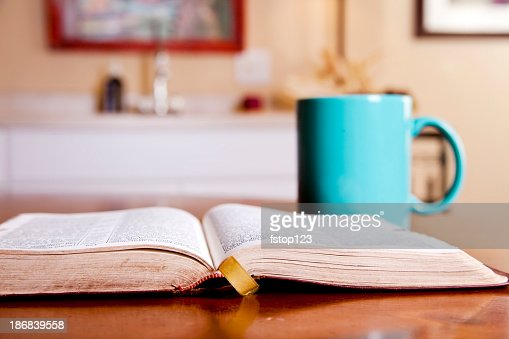Open Bible on kitchen table with coffee mug