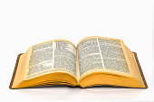 Open bible on plain white background with yellowed pages and small text