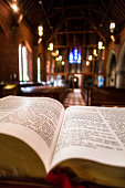 Close up image of the Holy Bible open on the altar of an Anglican church. The pews and stained glass windows of the interior of the church are blurred out of focus in the background, and warm orange s