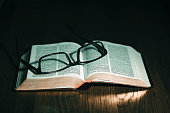 Open Bible with glasses on top over a wooded table.
