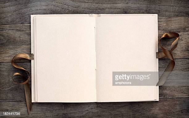 Open blank book on dark wooden table with a brown ribbon