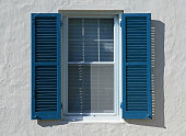 Open blue window shutters, against a white wall, in a hot country