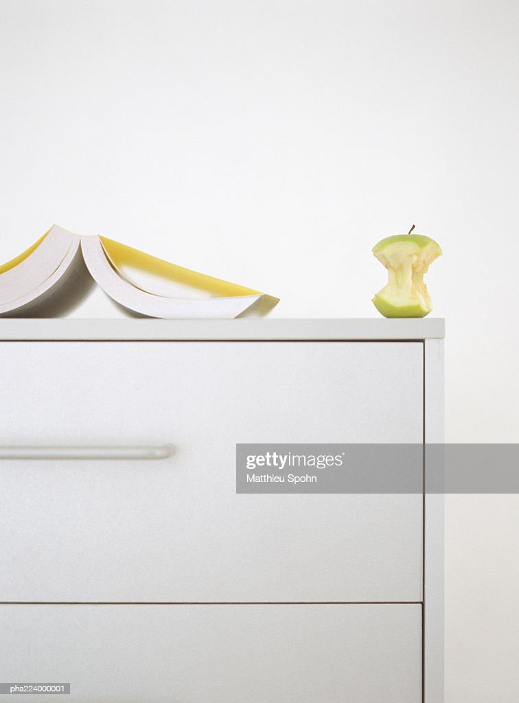 Open book and apple core on top of dresser.