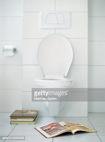Open book in front of toilet.
