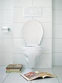 Open book in front of toilet.