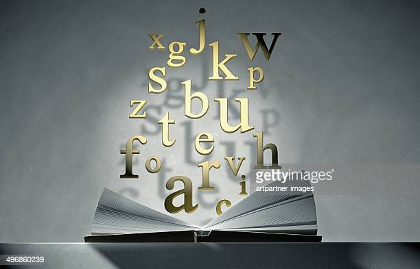 Open book on a table with floating golden letters