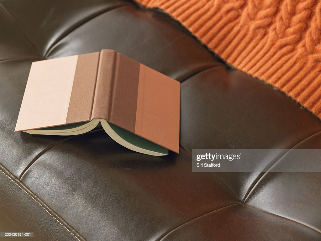 Open book on leather chair, elevated view : Stock Photo