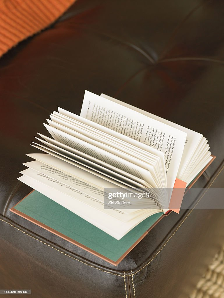 Open book on leather chair : Stock Photo