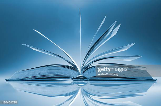 Open book on table with its pages fanned wide