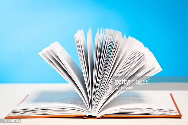 Open book, paging through pages lying on table, blue background