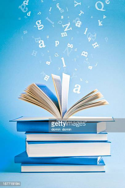Open book with flying, scattered letters isolated on blue background