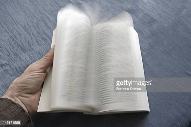Open book with pages turning, blurred motion