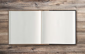 Open book on rustic wooden background. Minimal flat lay