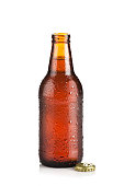 Full brown beer bottle isolated on white background with drops and condensation, back lit and showing a soft white reflection at right side. The bottle is opened and a golden cap is at the base of it.
