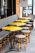 Traditional cafe in Paris with open terrace, round tables and wicker chairs, France