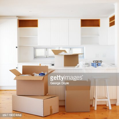 Open cardboard boxes kept in an empty kitchen : Stock Photo