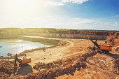 Open cast quarry, machines, excavators in quarry limestone mining in sunlight,