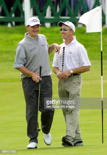 Open champion Paul Lawrie shares a joke with his caddy after a brief practice session at St Andrews on the final practice day of the Open Championship