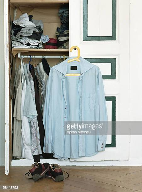 Open closet containing men's clothing