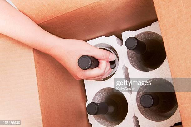 Ouvrir la boîte de livraison avec quatre bouteilles de vin