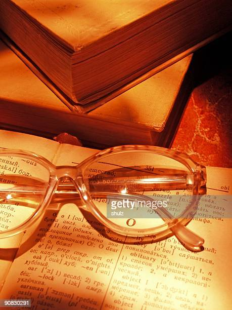 Open dictionary, glasses and books