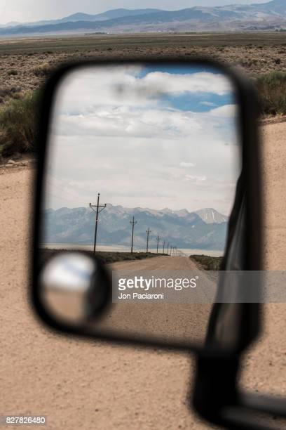 Open Dirt Road Reflected in a Rearview Mirror