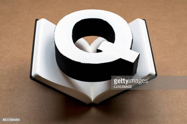 Open dummy book with the capital letter Q on it.