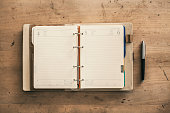 Open empty spiral hard cover notebook next to pen wooden background