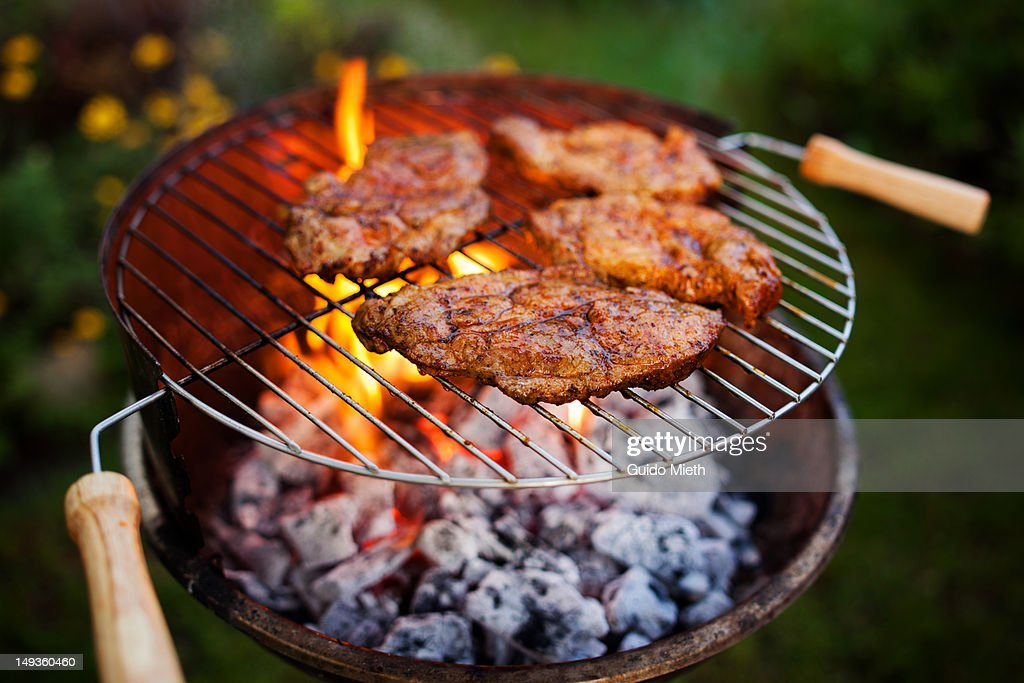 Open flame grill with steaks : Stock Photo