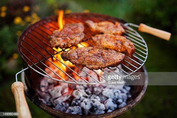Open flame grill with steaks