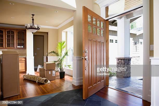 Open front door, rolled up rug and cartons on floor