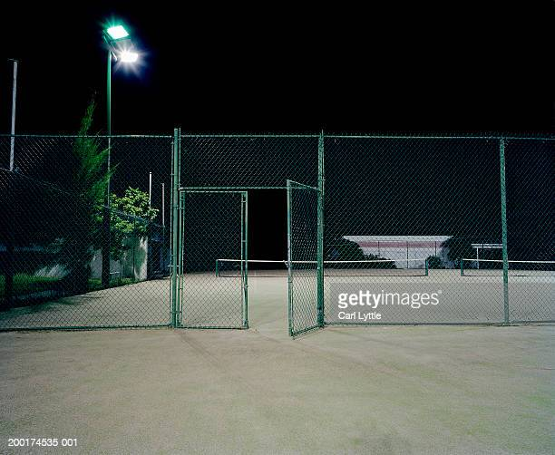 Open gate surrounding two tennis courts, night