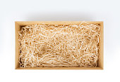 Open gift box with decorative straw for product display, top view