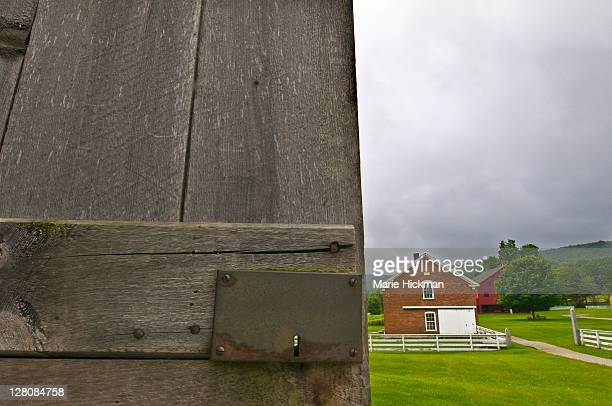 Open grey wooden barn door and lock of the barn at Hancock Shaker Village with a red brick building in background, Pittsfield, Massachusetts, USA