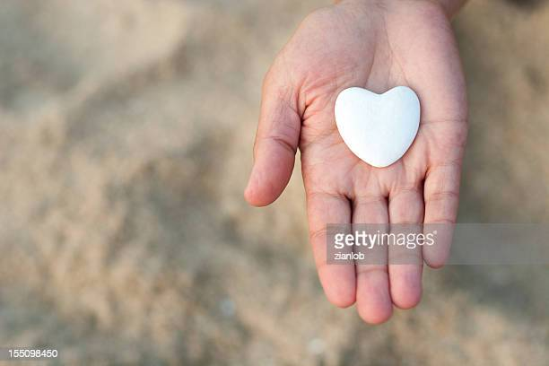 Open hand holding a heart on defocused sand background.