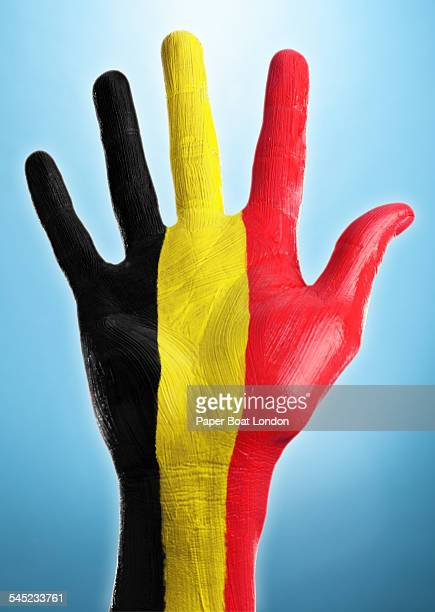 Open hand with flag of Belgium painted on it