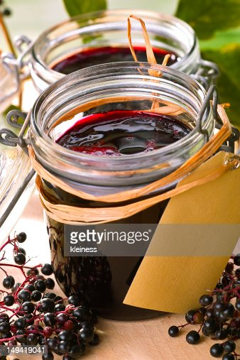 Open jars of fresh elderberry jam with paper tags : Stock Photo