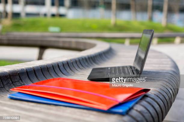 Open laptop and paperwork files on bench, outdoors