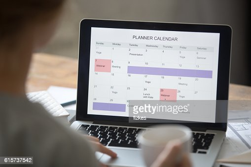 Open Laptop On The Desk Planner Calendar On The Screen Stock Photo