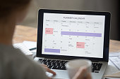 Open laptop on the desk with a planner calendar on the screen. Education concept photo, view over the shoulder, close up