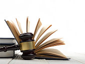 Law concept - Open law book with a wooden judges gavel on table in a courtroom or law enforcement office isolated on white background. Copy space for text.