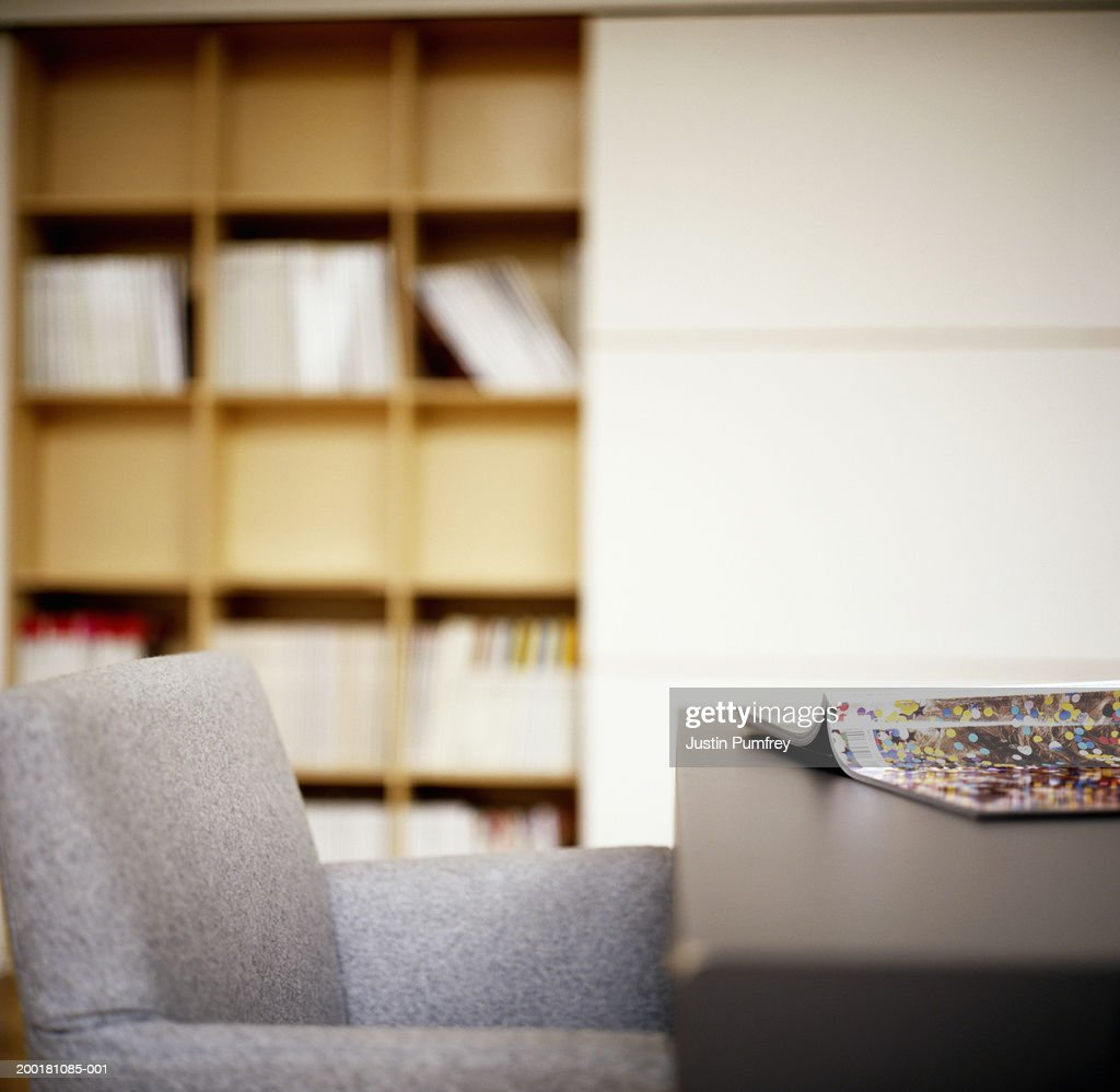 Open magazine on table by armchair, indoors : Stock Photo